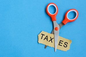 Scissor Cutting Taxes Word on Paper
