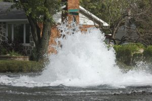 Street and home flood by major underground water pipe failure.